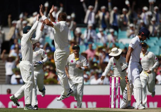 England's captain Cook reacts, as Australia's Harris celebrates with teammates, after being dismissed for seven runs during the second day of the fifth Ashes cricket test at the Sydney cricket