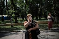 A woman cries while her relative is evacuated by bus from the town of Makiyivka, eastern Ukraine on August 18, 2014