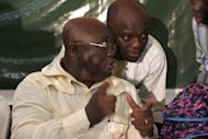 Ghana opposition presidential candidate Nana Akufo-Addo talks to an aide during press conference in Accra on December 28, 2012. Ghana's main opposition, alleging electoral fraud, filed a court challenge today to results from this month's presidential polls handing victory to incumbent John Dramani Mahama.