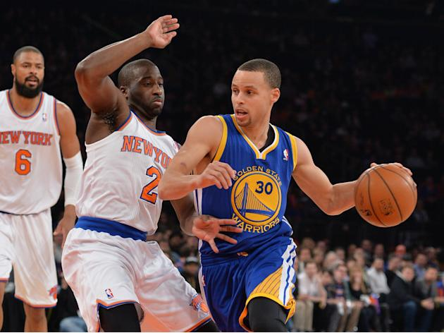 El base Stephen Curry, de los Golden State Warriors (D) conduce el balón ante la marca de Raymond Felton (C) de los New York Knicks, en partido jugado en el Madison Square Garden, en Nueva York el 28