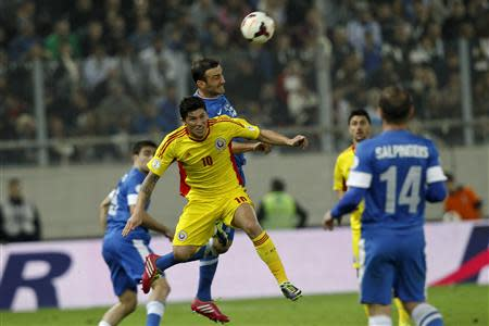 Romania's Tanase jumps for the ball against Greece's Torosidis during their 2014 World Cup qualifying playoff first leg soccer match in Athens