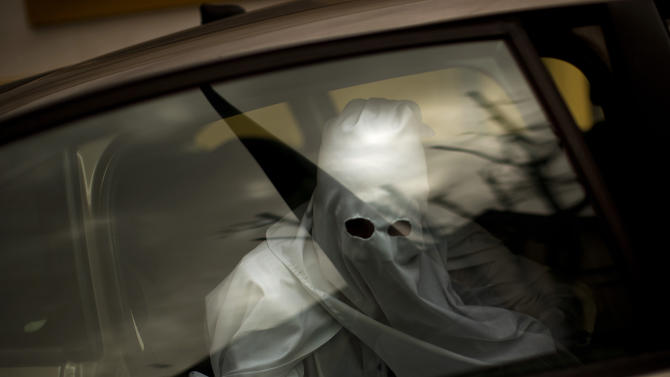 A penitent from the La Paz brotherhood is seen inside a car as he arrives to the church to take part in a procession in Seville, Spain, Sunday, March 24, 2013. Hundreds of processions take place throughout Spain during the Easter Holy Week. (AP Photo/Emilio Morenatti)