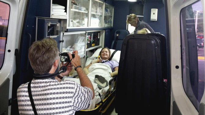 In this image provided by Tom Adkins, Andy Copeland takes a photo of his daughter, Aimee, as she leaves a hospital in Augusta Ga., Monday, July 2, 2012, headed for an inpatient rehabilitation clinic. Copeland left a Georgia hospital just weeks after a flesh-eating disease took her limbs but not her life. After nearly two months of battling the rare infection, called necrotizing fasciitis, Copeland headed to an inpatient rehabilitation clinic, where she'll learn to use a wheelchair after having her left leg, right foot and both hands amputated. (AP Photo/Tom Adkins)