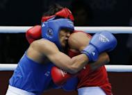 Serdar Hudayberdiyev (R) of Turkmenistan and Manoj Kumar (L) of India clinch during their first round Light-Welterwight (64kg) boxing match of the London 2012 Olympics at the ExCel Arena in London. Kumar was awarded a 13-7 points decision