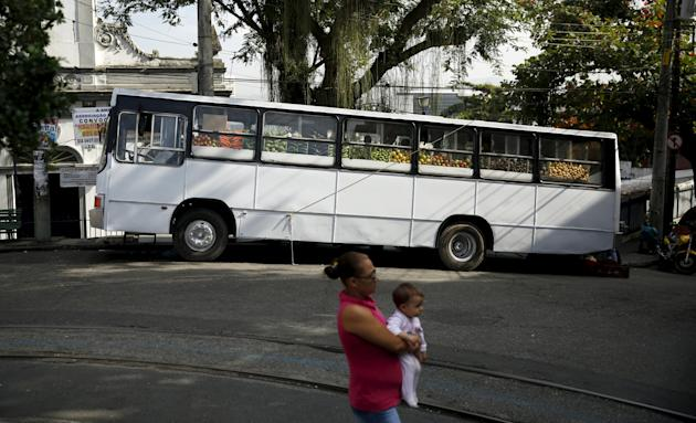 A woman holds her baby as she stands in front of a bus market called Sacolao in Santa Teresa neighborhood in Rio de Janeiro