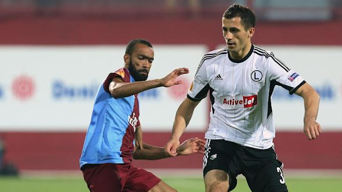 Trabzonspor's Zyro, left, and Bosingwa of Legia fight for the ball during their Europa League Group J soccer match in Trabzon, Turkey, Thursday, Oct. 24, 2013. (AP Photo)