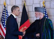 Afghan President Hamid Karzai (R) shakes hands with US President Barack Obama after signing a strategic partnership agreement at the Presidential Palace in Kabul. Obama landed in Afghanistan under a veil of secrecy and high security, and signed a post 2014 partnership deal with Kabul, a year to the day after the killing of Osama bin Laden