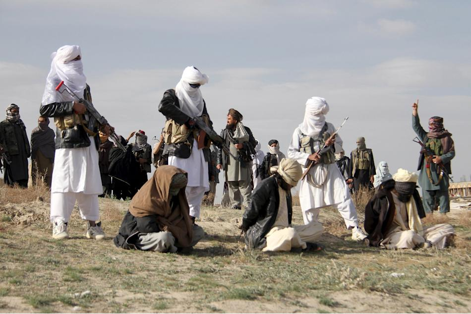 Taliban insurgents stand over three men, accused of murdering a couple during a robbery, before shooting them during their execution in Ghazni Province
