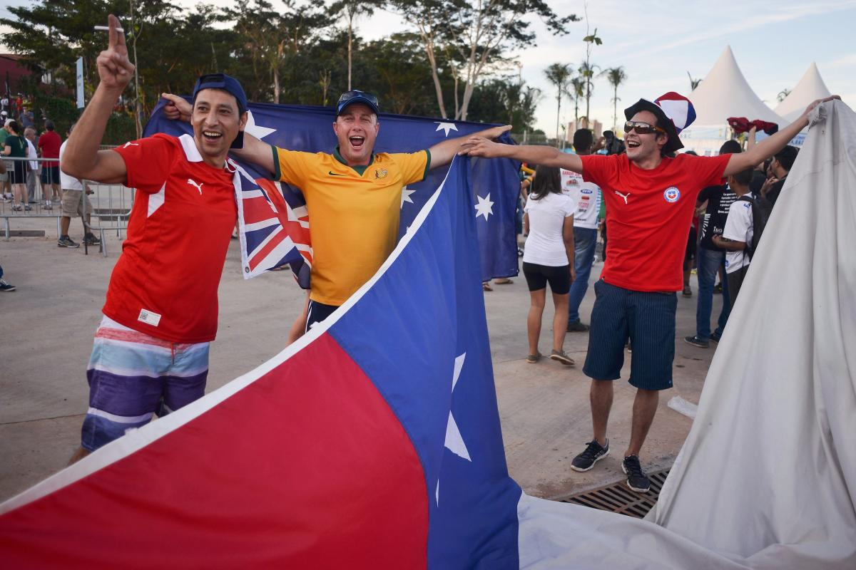 Chile and Australia fans party outside the Arena Pantanal soccer stadium in Cuiaba