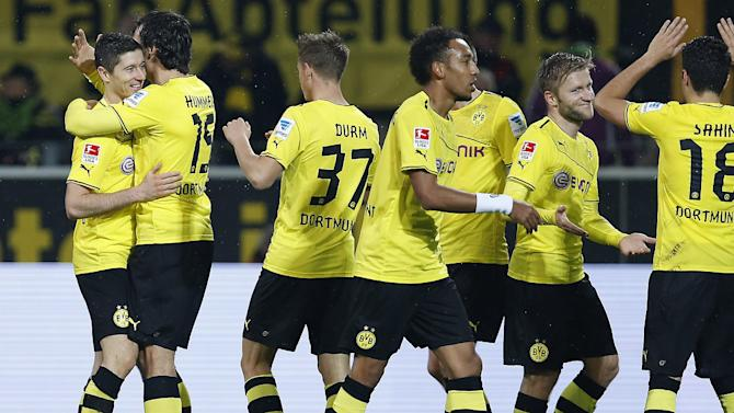 Dortmund's Robert Lewandowski of Poland, left, celebrates with teammates after scoring during the German first division Bundesliga soccer match between  BvB Borussia Dortmund and VfB Stuttgart  in Dortmund, Germany, Friday Nov. 1, 2013