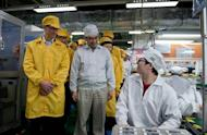 "Handout picture released by Apple and taken March 28, shows Apple chief executive Tim Cook (L) visiting the iPhone production line at the newly built Foxconn factory in Zhengzhou, China's north-central Henan province. Workplace abuses were uncovered in an audit that equated to ""a full body scan"" of three Chinese factories pumping out coveted Apple gadgets, independent investigators reported"