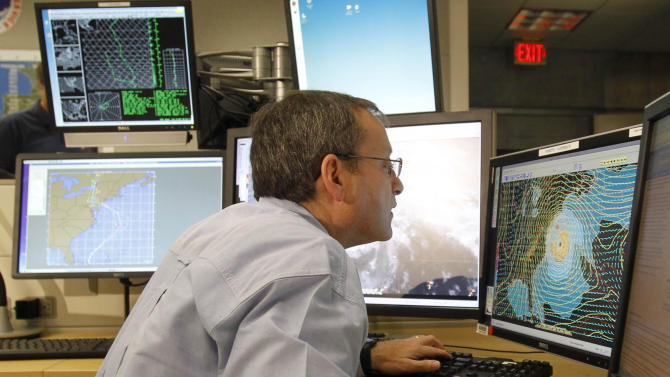 FILE - In this Sunday, Oct. 28, 2012 file photo, chief hurricane specialist James Franklin looks at computers tracking Hurricane Sandy at the National Hurricane Center in Miami. In just two weeks this fall, computer models displayed an impressive prediction prowess, from predicting Superstorm Sandy to who would win the U.S. presidential election. (AP Photo/Alan Diaz, File)