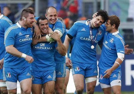 Italy's players celebrate after winning against Ireland at the end of their Six Nations international rugby union match at the Olympic Stadium in Rome