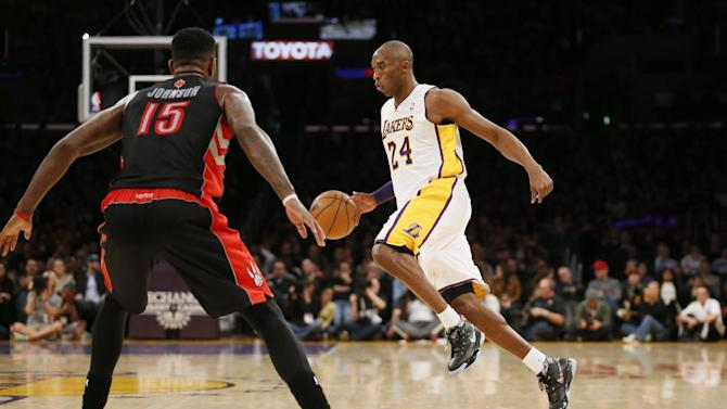 Los Angeles Lakers' Kobe Bryant dribbles the ball as Toronto Raptors' Amir Johnson, left, defends during the first half of an NBA basketball game in Los Angeles, Sunday, Dec. 8, 2013