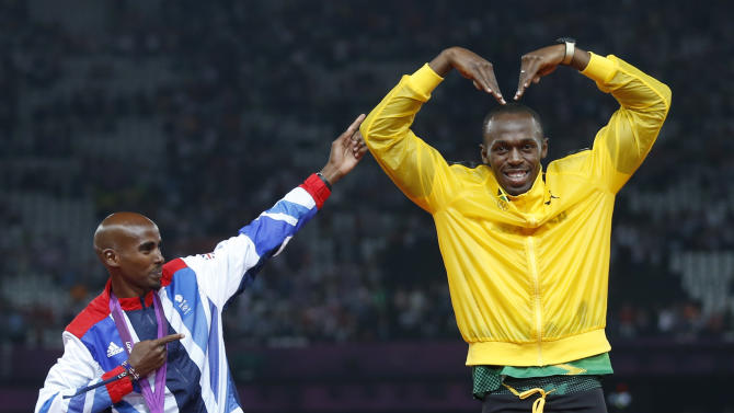 Jamaica's Bolt celebrates with Britain's Farah on the podium after each receiving gold medals, Bolt for men's 4x100m relay and Farah for men's 5000m at the victory ceremony at the London 2012 Olympic Games