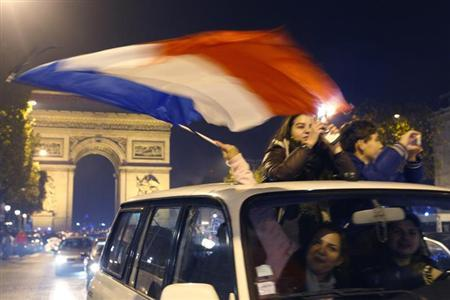 France soccer fans celebrate with their country's flag near the Arc de Triomphe on the Champs Elysees in Paris after France defeated Ukraine in their 2014 World Cup qualifying second leg playoff soccer match, November 19, 2013.
