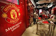 Manchester United fans from Thailand look inside a souvenir shop in Bangkok