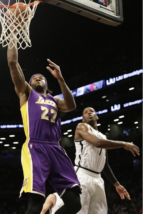 Los Angeles Lakers center Jordan Hill (27) goes to the basket past Brooklyn Nets forward Joe Johnson (7) during the first half of an NBA basketball game, Sunday, March 29, 2015, at  New York.  (AP Pho