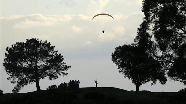A paraglider sails over a golfer as he tees off during the weather delayed fourth round of play at the Farmers Insurance Open in San Diego, California (Reuters)