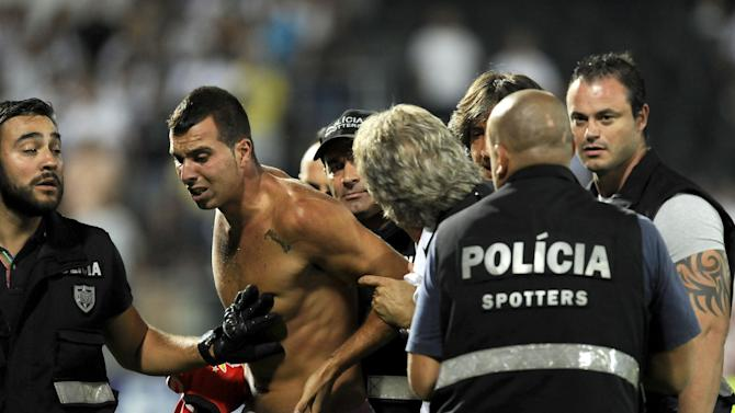 Benfica's coach Jorge Jesus, center right, tries to stop a fan from being arrested by police after a pitch invasion, during the Portuguese League soccer match between Benfica and Vitoria Guimaraes at D. Afonso Henrique stadium in Guimaraes, Portugal, Sunday, Sept. 22, 2013. Benfica won 1-0