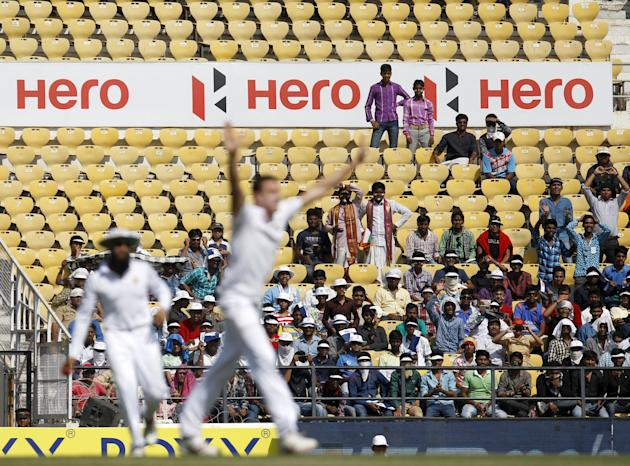 Spectators watch as South Africa's Morkel raises his arms to celebrate taking the wicket of India's Vijay during the second day of their third test cricket match in Nagpur