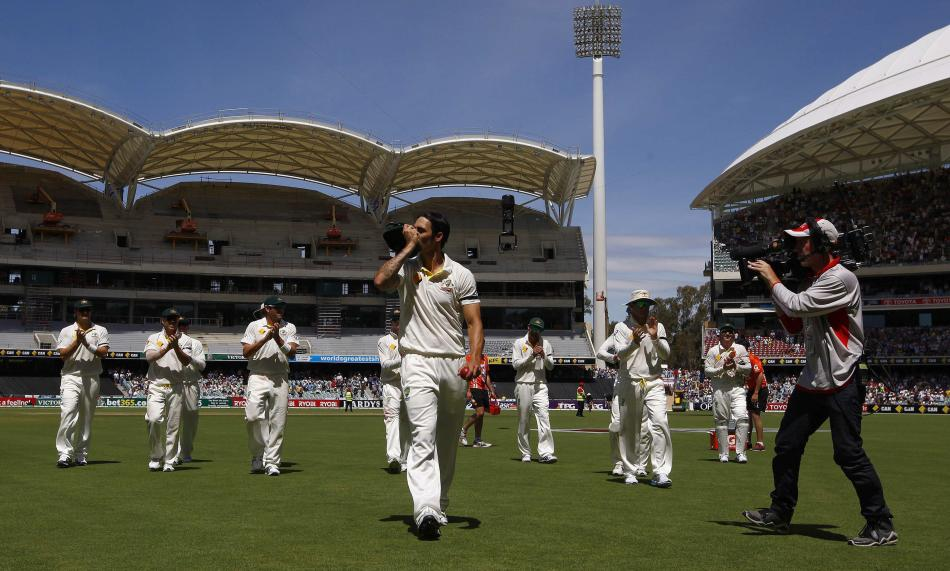 Australia's Johnson kisses his cap after taking seven wickets in the inning during the third day's play in the second Ashes cricket test against England at the Adelaide Oval
