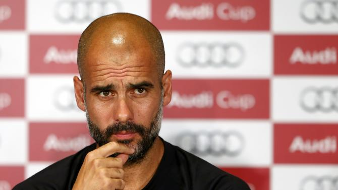 Coach Guardiola of Bayern Munich looks on during a news conference on the eve of their pre-season Audi Cup tournament, in Munich