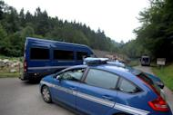 """Vehicles of French gendarmerie drive on the """"Combe d'Ire"""" road in the French Alpine village of Chevaline. Three of the four people killed in a mystery shooting in the French Alps were shot in the head in what the prosecutor in charge of the case called an act of """"extreme savagery."""""""