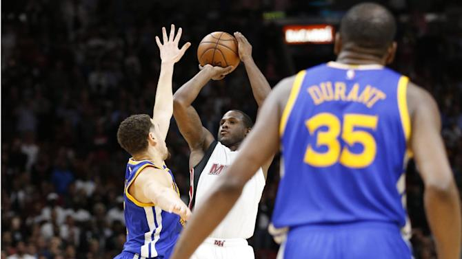 Miami Heat guard Dion Waiters, center, goes up for a three-point shot against Golden State Warriors guard Klay Thompson, left, as forward Kevin Durant (35) looks on during the last with 0.6 seconds of an NBA basketball game, Monday, Jan. 23, 2017, in Miami. Waiters had 33 points as the Heat defeated the Warriors 105-102. (AP Photo/Wilfredo Lee)