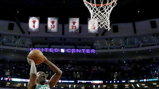 Boston Celtics guard Jordan Crawford (27) scores as teammate Avery Bradley (0) and Chicago Bulls guard D.J. Augustin, right, watch during the second half of an NBA basketball game on Thursday, Jan. 2, 2014, in Chicago. The Bulls won 94-82