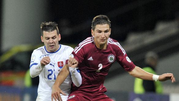 Latvia's Vitalijs Maksimenko, right,   vies for the ball with Slovakia's Michal Duris during a World Cup 2014 Group G qualification match in Riga, Latvia, on Tuesday. Oct. 15, 2013