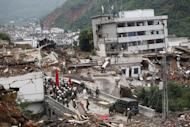 Rescuers walk towards damaged houses and debris after the earthquake in Ludian county in Zhaotong, southwest China's Yunnan province on August 4, 2014