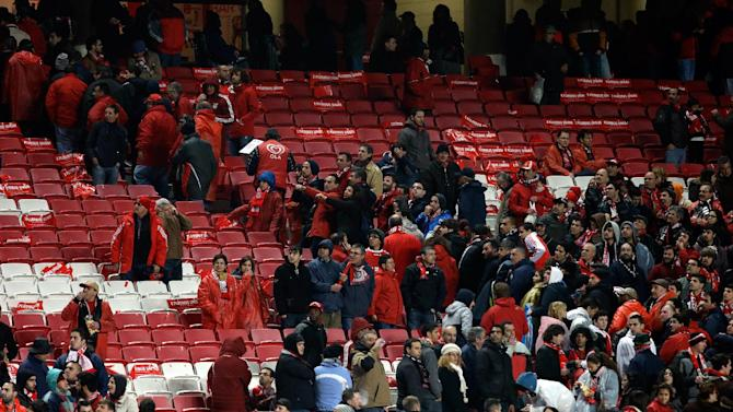 Spectators leave the stands after being asked to do so before the start of the Portuguese league soccer match between Benfica and Sporting Sunday, Feb. 9 2014, at Benfica's Luz stadium in Lisbon. Strong winds damaged the stadium roof before kick off and debris fell on the pitch and stands. It was decided the match should be postponed for security reasons