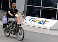A man rides a motobike past the logo of Google's China headquarters in Beijing in 2010. Google said Friday that it would stop providing music search and download services in China from next month after a disappointing response from users