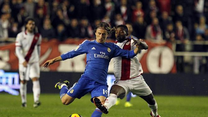 Real Madrid's Luka Modric, from Croatia, tussles for the ball with Rayo Vallecano's Lass Bangoura, right, from Guinea Conakry, during the Spanish La Liga soccer match between Real Madrid and Rayo Vallecano at the Vallecas stadium in Madrid, Saturday, Nov. 2, 2013. Real Madrid won 3-2