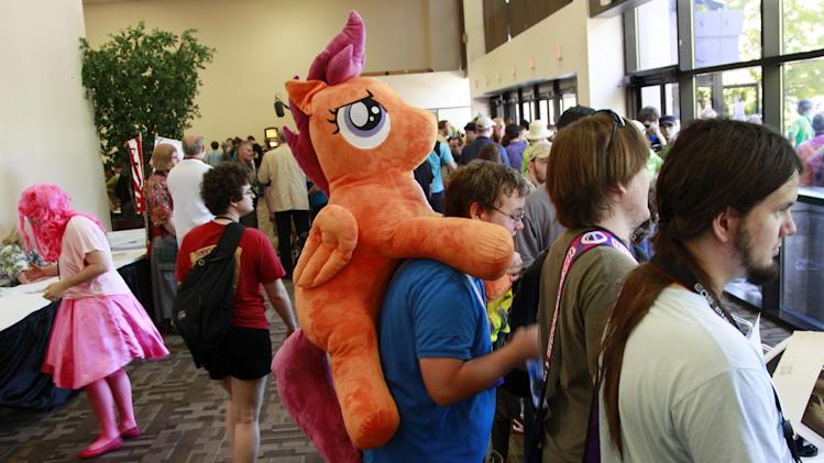 "Matthew Zadonia carries a stuffed animal from the My Little Pony cartoons as he stands with others at ""BronyCon"" Saturday, June, 30, 2012, in Secaucus, N.J. Scores of men in brightly colored costumes were among the 4,000 My Little Pony fans at this weekend's ""BronyCon"" gathering in New Jersey for fans of a My Little Pony cartoon.  (AP Photo/Mel Evans)"