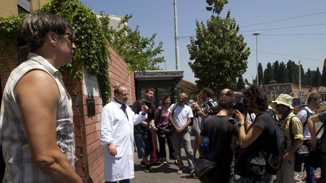 Coroner Antonio Spasola, center in white medical gown, speaks to the media outside the morgue of Policlinico Umberto I hospital where the body of actor James Gandolfini was brought after he died late Wednesday in Rome,Thursday, June 20, 2013. Gandolfini died after suffering a cardiac arrest while vacationing in Rome. Claudio Morini, head of the hospital's emergency room, said Gandolfini arrived at the hospital at 10:40 p.m. (2040 GMT, 4:40 p.m. EDT) Wednesday and was pronounced dead at 11 p.m. after resuscitation efforts in the ambulance and hospital failed. (AP Photo/Alessandra Tarantino)