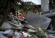 Mexican rescuers search for victims amid the debris of the Pemex headquarters in Mexico City, on February 1, 2013. The death toll in a mystery explosion at the headquarters of Mexico's state-owned oil giant Pemex rose to 32 as rescuers dug through the rubble