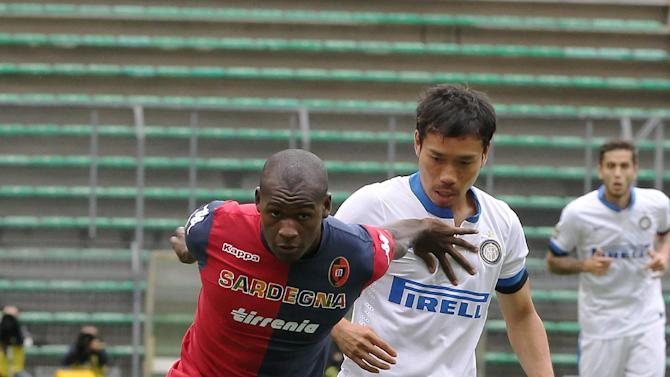 Cagliari's Victor Ibarbo, left, of Colombia, holds back Inter Milan Japanese defender Yuto Nagatomo, challenge for the ball during the Serie A soccer match between Cagliari and Inter, at the Nereo Rocco Stadium in Trieste, Italy, Sunday, Sept. 29, 2013