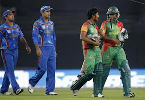 Bangladesh's Shakib Al Hasan (R) and Anamul Haque come leave field as Afghanistan's players watch, after Bangladesh won the ICC Twenty20 World Cup match at the Sher-E-Bangla National Cricket Stadium in Dhaka March 16, 2014. REUTERS/Andrew Biraj