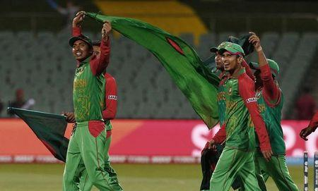 Bangladesh's Soumya Sarkar carries his nation's flag alongside team mates after they defeated England in their Cricket World Cup match in Adelaide