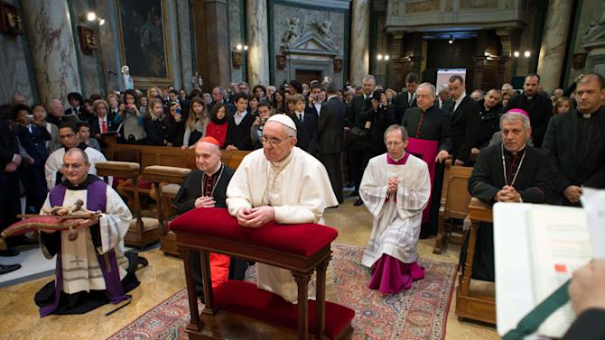In this photo provided by the Vatican paper L'Osservatore Romano, Pope Francis kneels at the Vatican St. Anna parish church, Sunday, March 17, 2013. Pope Francis began his first Sunday as pontiff by making an impromptu appearance to the public from a side gate of the Vatican, startling passersby and prompting cheers, then kept up his simple, spontaneous style by delivering a brief, off-the-cuff homily at the Vatican's tiny parish church. Dressed only in white cassock, Francis waved to the crowd in the street outside St. Anna's Gate and before entering the church, which serves Vatican City State's hundreds of residents, he shook hands of the parishioners and kissed babies. (AP Photo/L'Osservatore Romano)