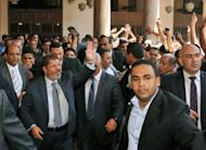 In this handout picture made available by the Egyptian presidency, president-elect Mohamed Morsi (left) waves to supporters after the weekly prayers at Cairo's historic Al-Azhar mosque on the eve of his swearing-in as Egypt's first civilian president