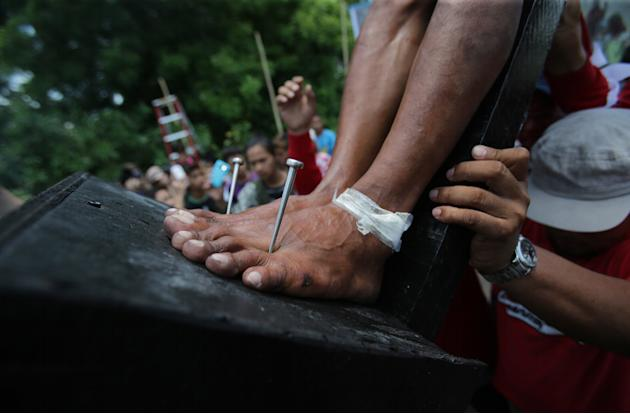A Filipino devotee with his feet nailed to the cross is lifted as they try to re-enact the crucifixion of Jesus Christ in San Juan village, Pampanga province, northern Philippines on Friday, April 18,