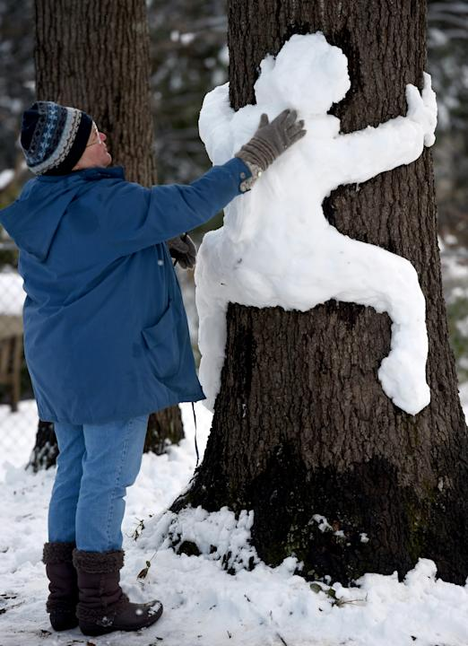 Robin Fulford puts the finishing touches on a snow sculpture in her yard, Thursday, Feb. 26, 2015, in Huntsville, Ala. A record winter storm that dumped a foot of snow on north Alabama left roads coat