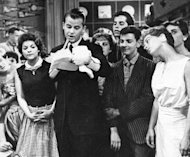 "FILE - In this 1957 file photo, Dick Clark is seen surrounded by fans during a television broadcast of ""American Bandstand."" Clark, the television host who helped bring rock `n' roll into the mainstream, died Wednesday, April 18, 2012 of a heart attack. He was 82. (AP Photo/File)"
