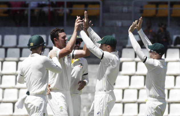 Australia opening bowler Josh Hazlewood, second left, high fives with teammates after taking the wicket of West Indies' opening batman Kraigg Brathwaite, who was caught by Brad Haddin for 10 runs,