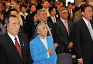 Exiled president of the World Uighur Congress Rebiya Kadeer, centre, listens to the national anthem at the opening session of the fourth World Uighur Congress in Tokyo. Kadeer says her people face a fight for their very existence against Chinese repression as a conference in Japan threatens to drive a wedge between Tokyo and Beijing