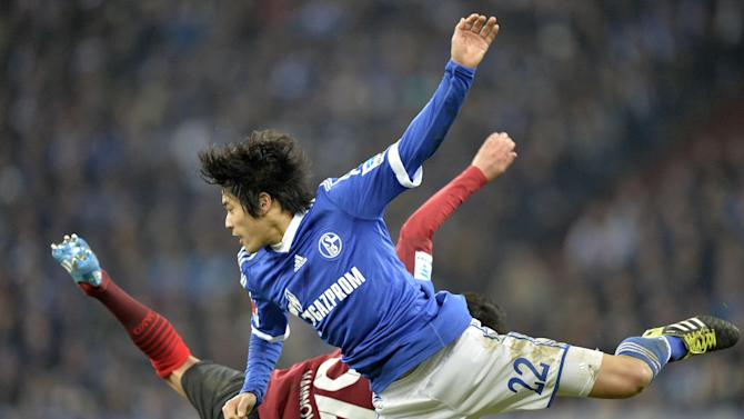 Schalke's Atsuto Uchida, in front, jumps with Hannover's Leonardo Bittencourt during the German Bundesliga soccer match between FC Schalke 04 and SV Hannover 96 in Gelsenkirchen,  Germany, Sunday, Feb. 9, 2014