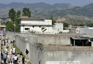 People gather outside the burnt compound where Al-Qaeda leader Osama bin Laden was killed by US Special Forces in 2011. A Senate panel voted to cut aid to Pakistan by a symbolic $33 million, $1 million for each year of jail time handed to a Pakistani doctor convicted of treason for helping track down bin Laden